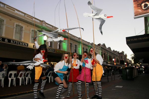 5 young people hold large seagull puppets on sticks