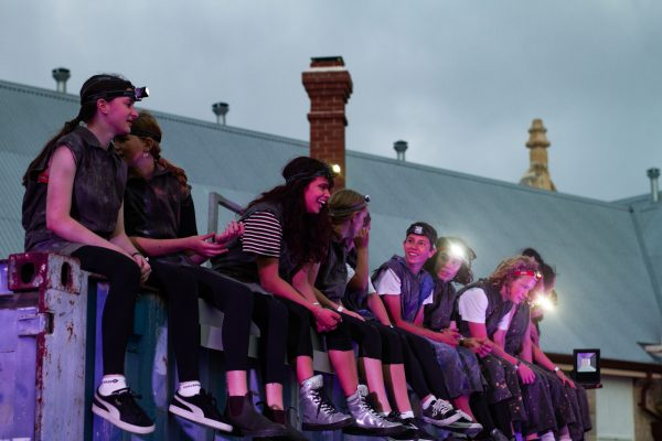 8 young people sit on top of a shipping container with headlamps on