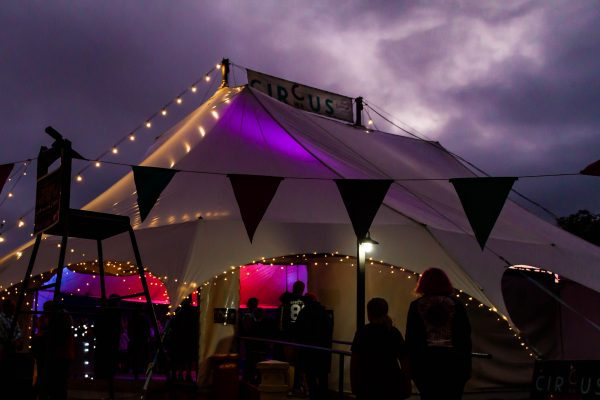 A circus tent is lit up with fairy lights as a purple hued thunderstorm rages