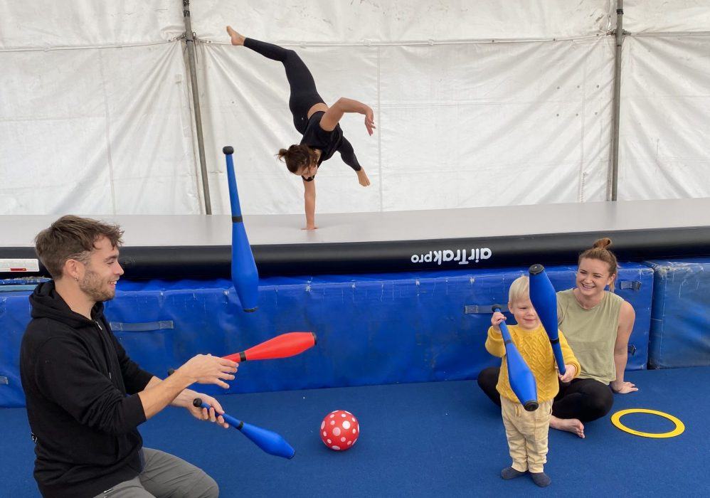 A man and a toddler juggle in the foreground while a woman watches, sitting cross legged in the middleground and a second woman cartwheels with one hand in the background
