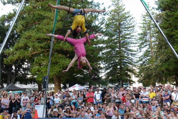 two girls hand upside down from an aerial troupe while a crowd watches below