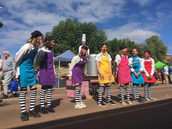 A row of 7 teenagers are dressed in brightly coloured aprons, striped socks and clown noses. behind them another teenager is on a platform with a chef's hat and a large cooking pot