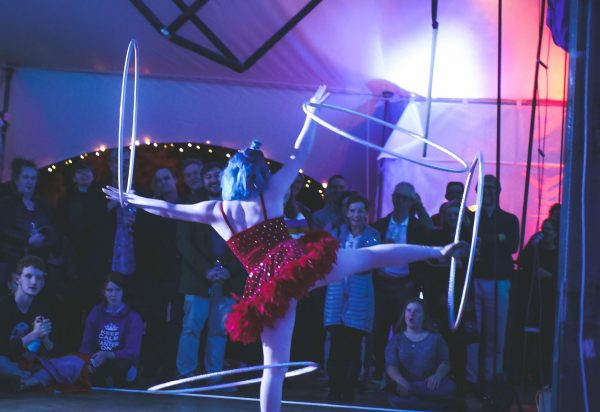 A girl in a red tutu spins hula hoops on both wrists and both ankles simultaneously