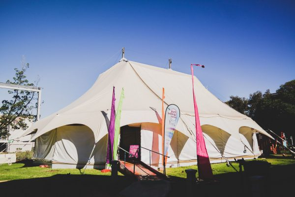 A white circus tent against a blue sky with colourful act-belong-commit banners at the entrance