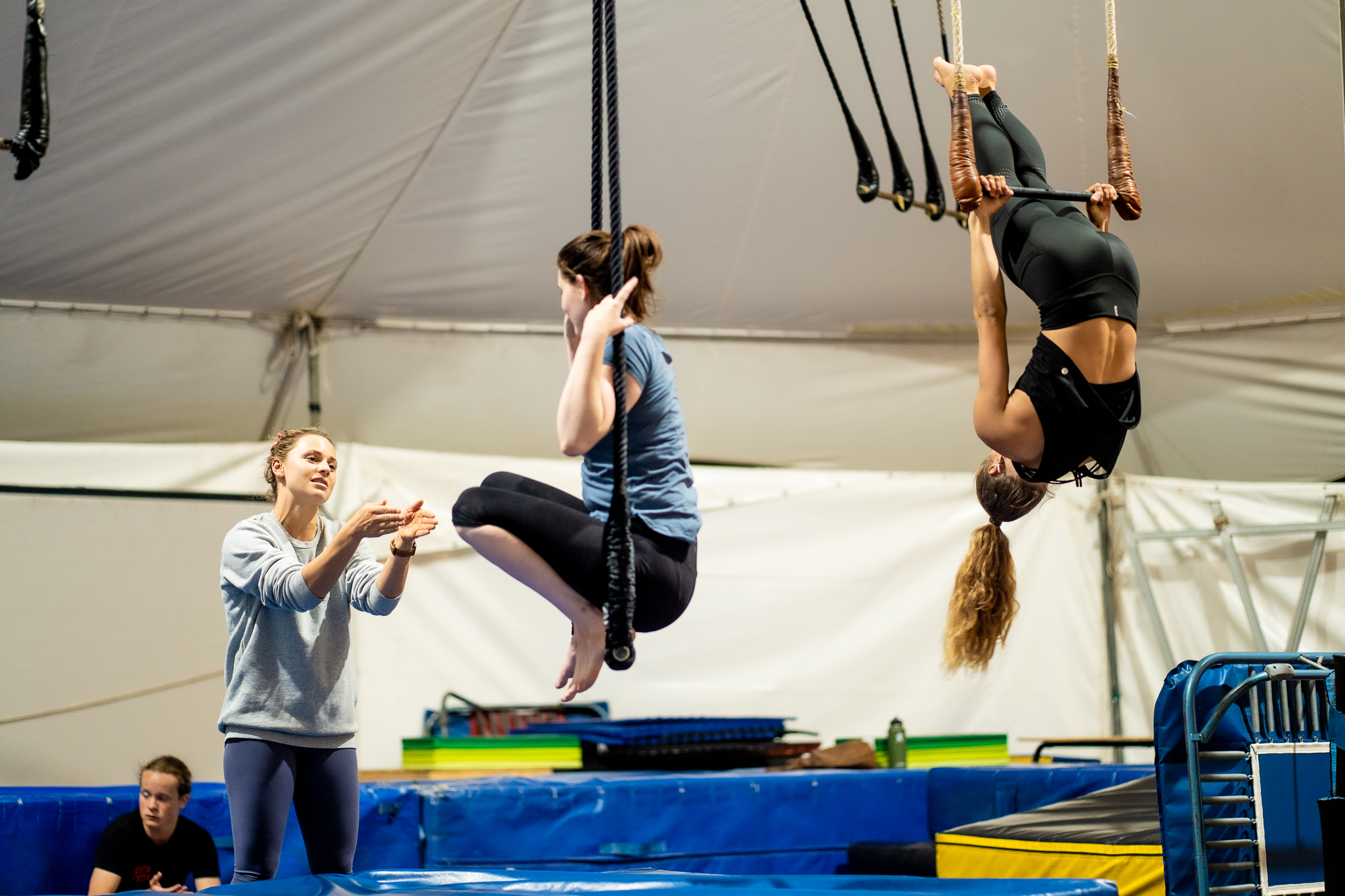 two people sit on trapezes listening to a trainer