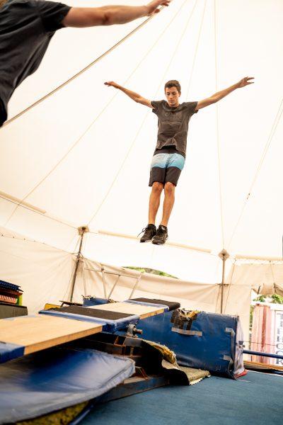 a teenager jumps on a teeterboard