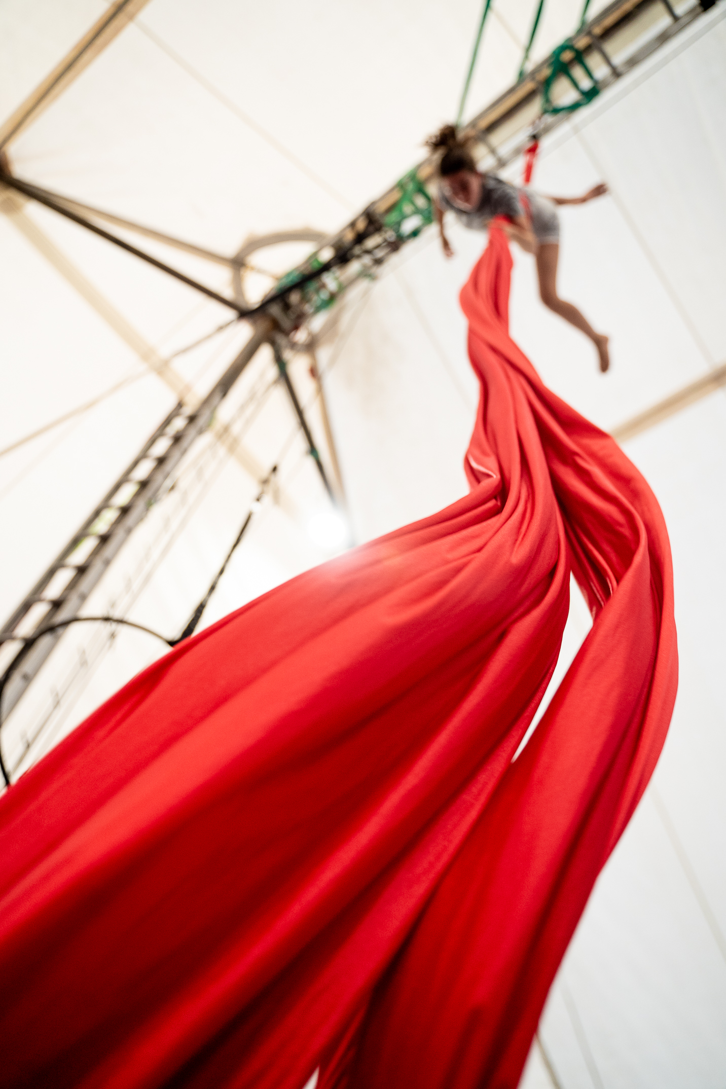 a distant figure is at the top of an aerial silk