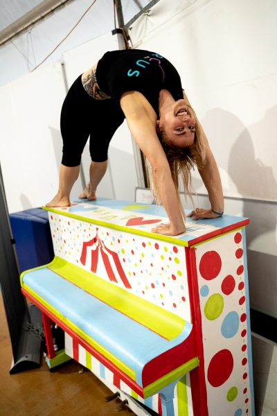a woman does a backbend on a brightly coloured piano