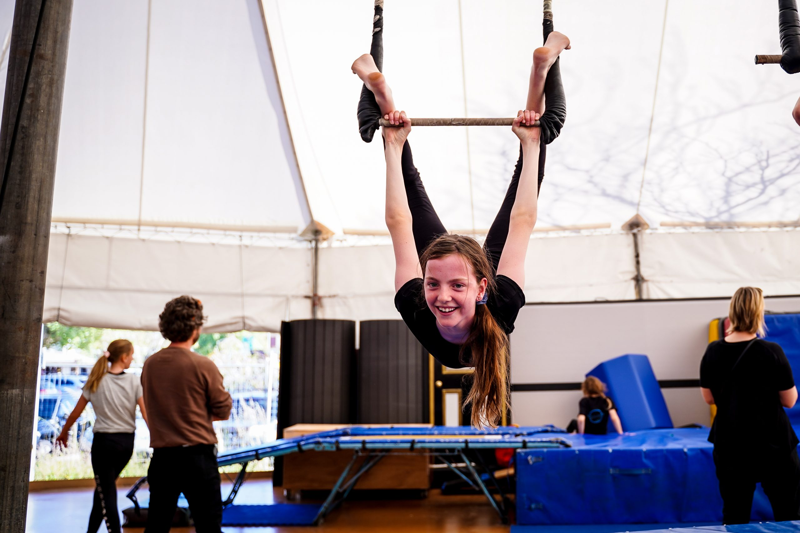 A girl hangs upside down from a trapeze