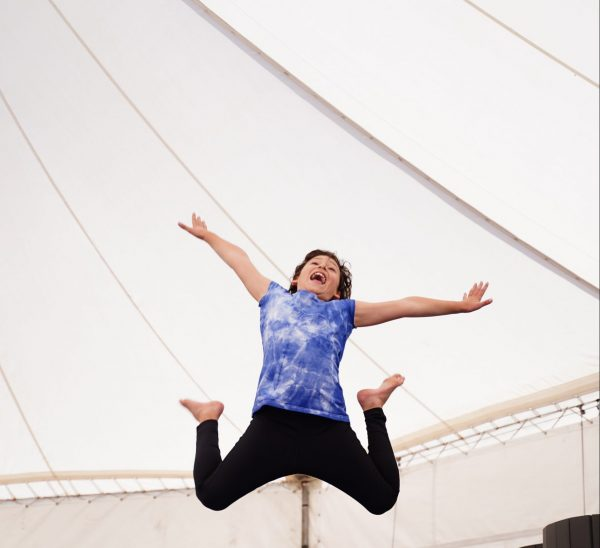 A child jumps exuberantly in the air