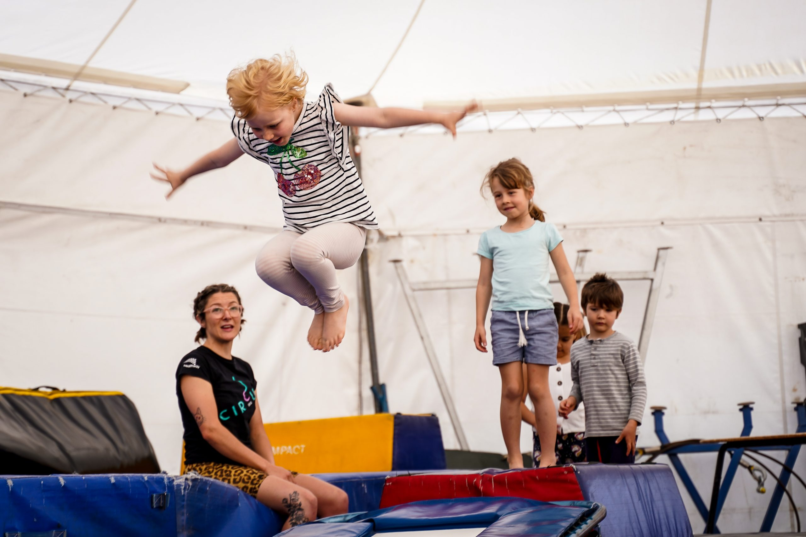 a child jumps on the trampoline while a trainer watches