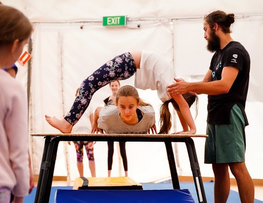 A girl aged approx 12 is holding a bendback on a table with a circus trainer supporting her shoulders while another girl the same age slides through the gap between the table and the first girls back.