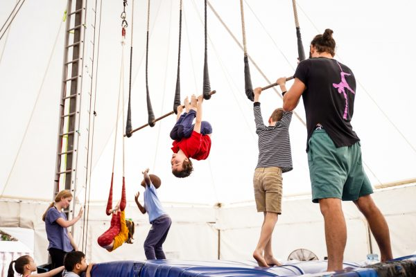 Several children aged approx 10yrs hang on trapezes, one in the middle is jumping to reach his trapeze bar, a trainer helps another boy onto the trapeze