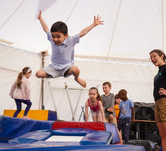 A boy approx 5yrs old jumps on a trampoline with this arms outstretched. Other children are lined up behind the tramp and his trainer looks on smiling