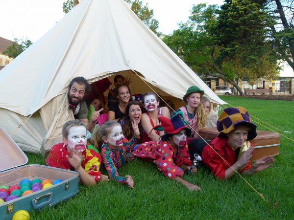 Several People crowd into a very small circus tent in a park
