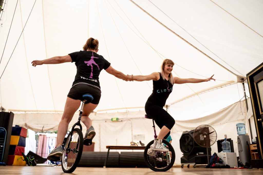 Two women hold hands and unicycle in a circle