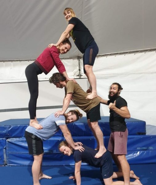 one adult kneels, one stands with his hands on the others shoulders and 3 additional adults stand on each others backs to form a pyramid. A trainer stands to the right, steadying one person higher on the pyramid with one hand and giving a thumbs up with the other.