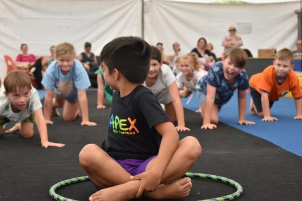 One boy sits in an aerial hoop while his friends crawl up behind him, trying not to be caught when he turns around