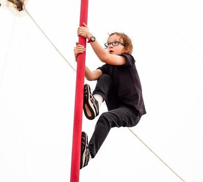 A boy climbs a red chinese pole